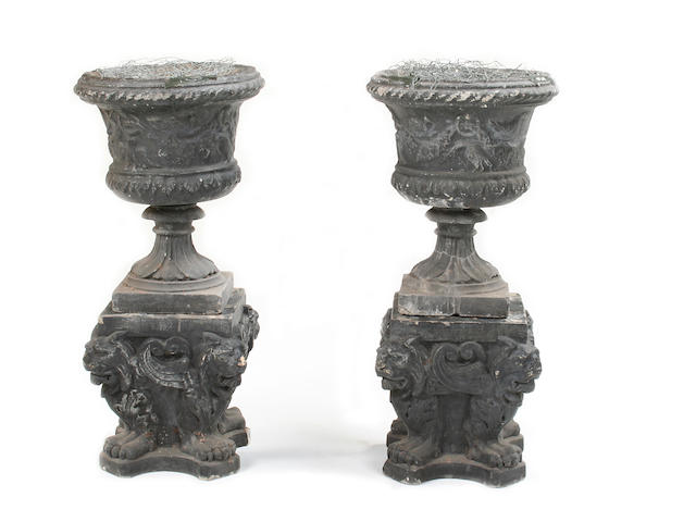 A pair of composition stone campana urns on stands
