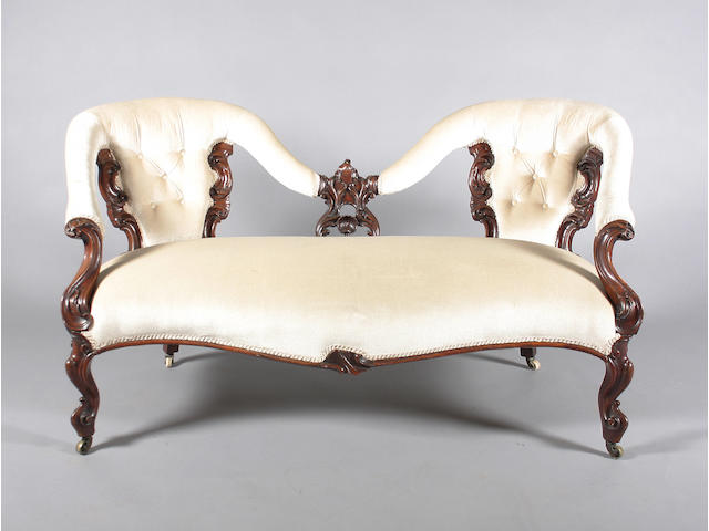 A Victorian rococo style carved walnut and button backed sofa