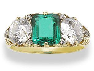 An emerald and diamond three-stone ring,