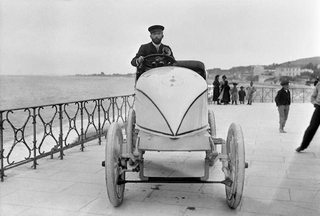 A limited edition monochrome photograph depicting a turn of the century Panhard racing car on a promenade,