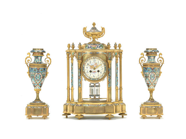 A late 19th century French champlevé enamelled mantel clock garniture Unsigned