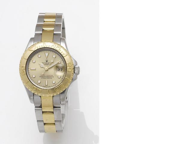 Rolex. A lady's stainless steel and gold automatic centre seconds calendar bracelet watch together with fitted box and papers Yachtmaster, Made in 1997, Sold December 31st 1998