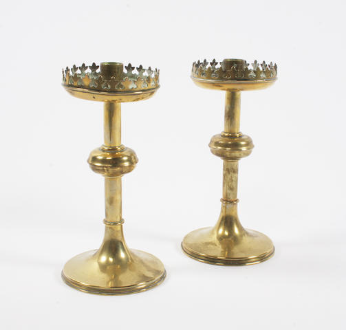 A pair of Gothic design brass candlesticks