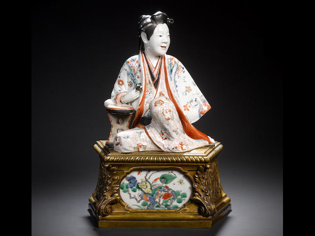 A rare ormolu-mounted Kakiemon model of a seated bijin The figure Japanese, Edo Period, circa 1670-1680, the ormolu mount French, probably Transitional-Louis XVI, circa 1760-1770, the plaque Chinese Kangxi, early 18th century