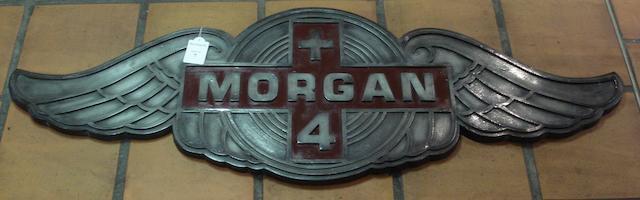 A cold-cast composite Morgan Plus 4 badge,