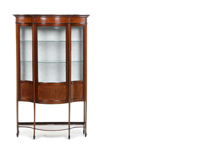 An Edwardian mahogany and satinwood banded serpentine display cabinet