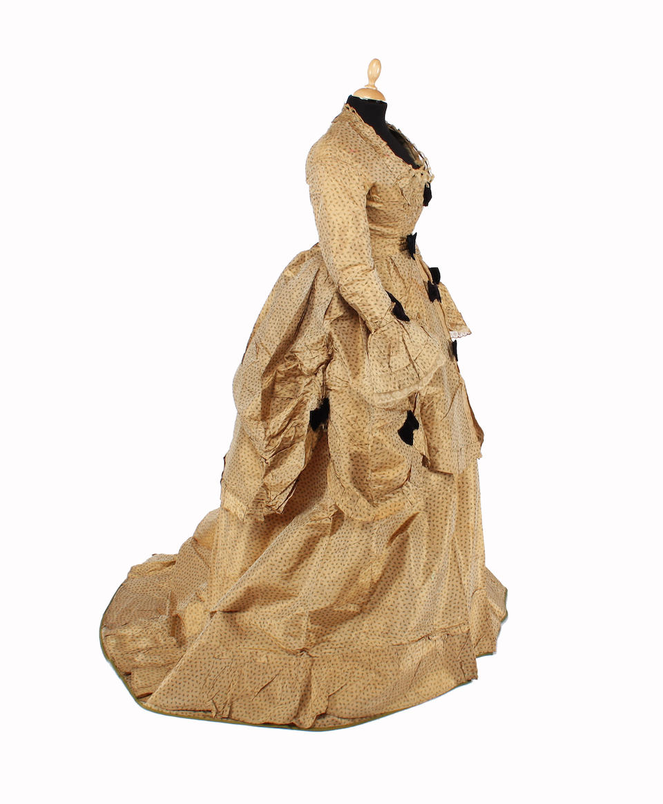 A late Victorian bustle back dress, of beige silk with a green fleck design