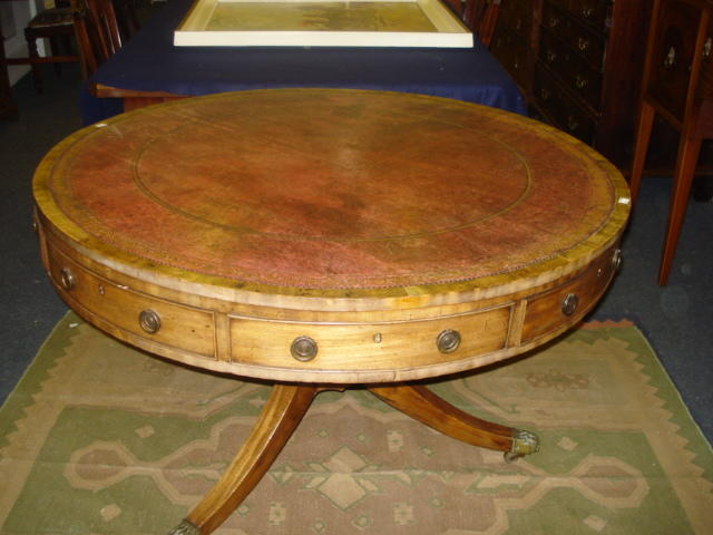A George III faded mahogany drum top library table, the inset top over four real and four alternate dummy drawers, on a tapering column and three sabre legs, 111cm diameter.