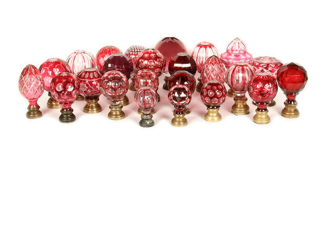 A collection of red and purple clear and opaque glass newel post finials