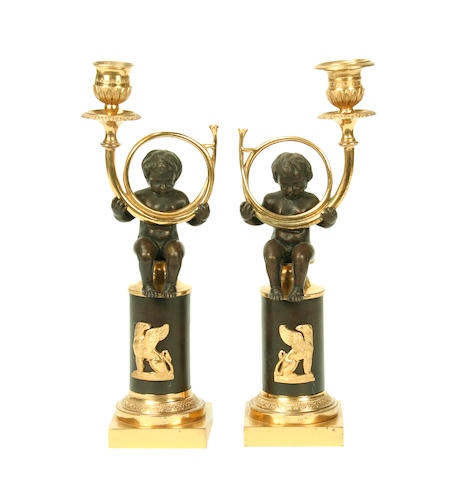 A pair of Directoire style patinated and gilt bronze figural candlesticks