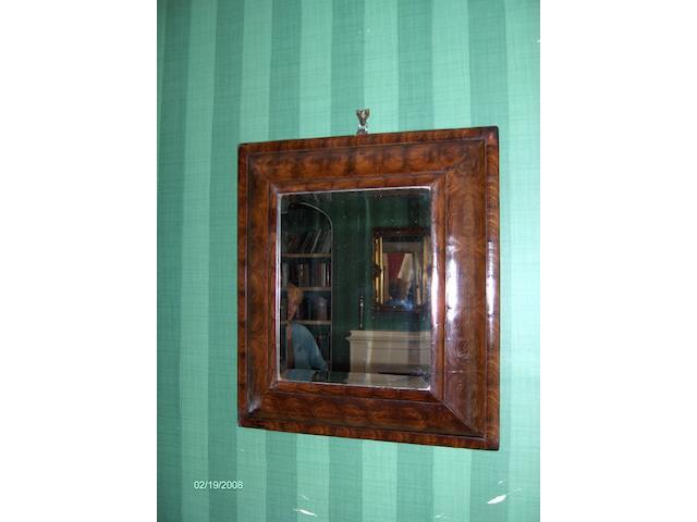 A William and Mary walnut oyster veneered cushion wall mirror