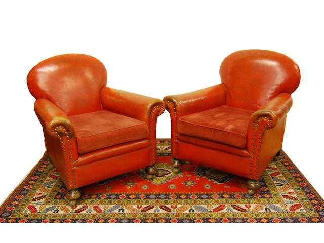 A pair of red leather-upholstered armchairs, early 20th Century
