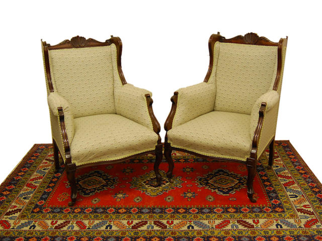 A pair of late Victorian mahogany-framed wingback armchairs