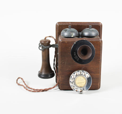A 1920s oak cased wall mounted twin bell telephone