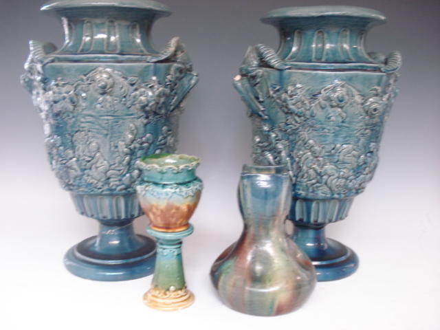 A pair of relief moulded pottery vases Probably French circa 1900