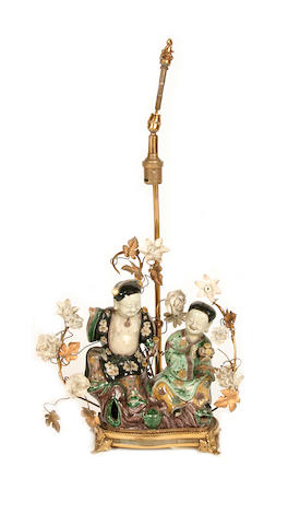 A 19th century Chinese famille verte ceramic group of the He He Erxian later mounted on a gilt bronze lamp base