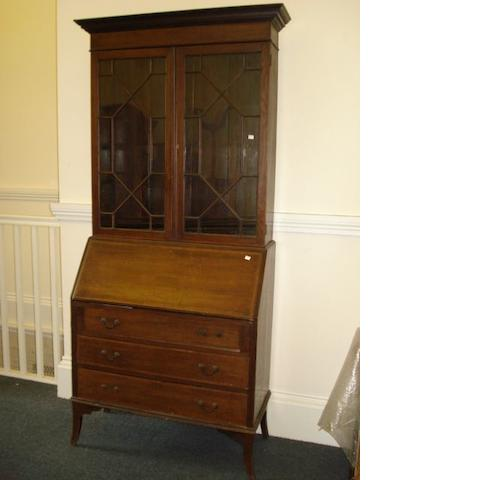 An early 20th Century inlaid oak bureau bookcase, the moulded cornice over double astagal glazed doors, on a bureau with thee long drawers on splayed legs.