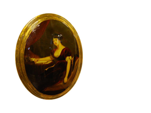 An oval ceramic plaque With printed scene portraying a seated lady reading a book, signed J. Crispan, in oval giltwood frame.