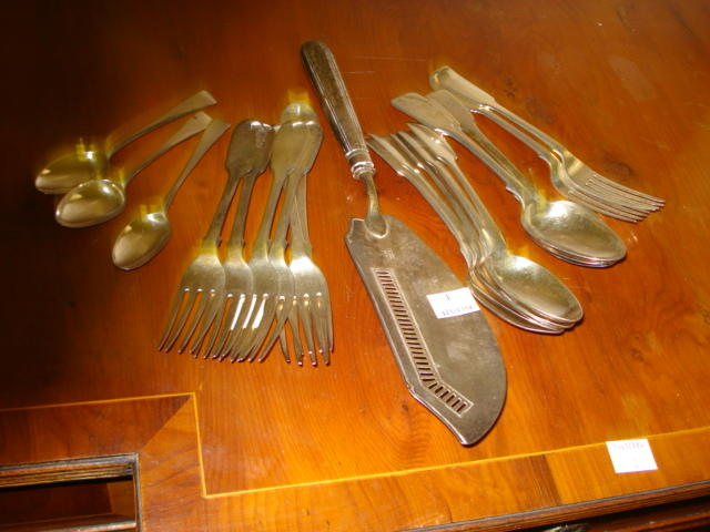 A set of seven William IV silver Fiddle pattern dessert forks, William Eaton, 1832, similar table fork, eight similar dessert spoons, including a pair James & Josiah Williams Exeter 1864, three Old English pattern silver teaspoons and a George III silver fish slice, William Eley & William Fearn, 1800, with thread pattern handle and slat pierced blade, weight 25oz.