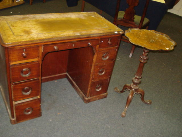 A Victorian mahogany kneehole desk, the moulded rectangular inset top above a single frieze and eight pedestal drawers, 101cm, and a Victorian walnut pedestal table, the shaped circular top on a turned, fluted and carved pillar and tripod base, 45cm. (2)