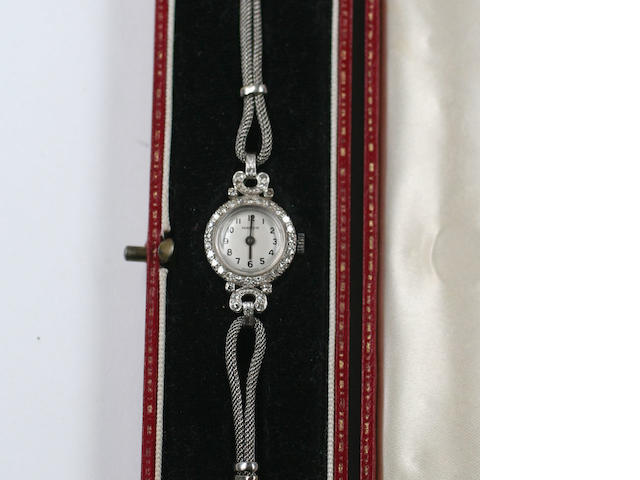 Marvin:  a lady's diamond set cocktail watch, circa 1940, circular dial within single cut diamond set bezel and shaped lugs on 9ct white gold plaited strap, cased.