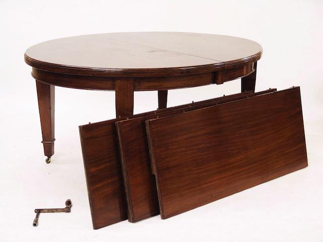 A late Victorian or Edwardian mahogany oval extending dining table,