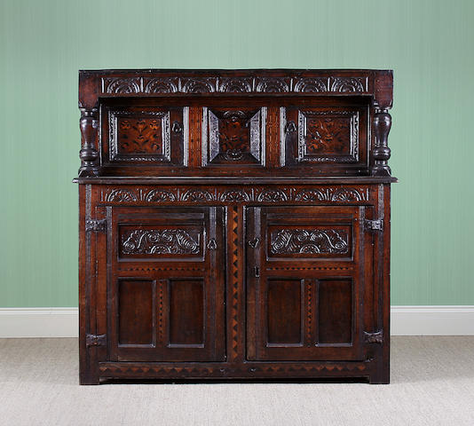 An early 17th Century inlaid oak court cupboard