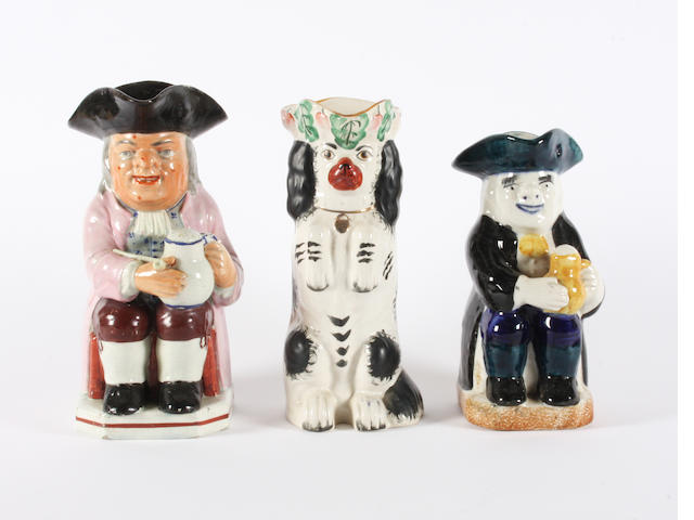 A pearlware Toby jug, a Staffordshire Toby jug and a Staffordshire jug in the form of a begging spaniel 19th Century.