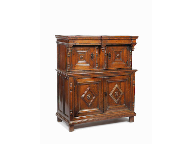 An oak small press cupboard,of 17th Century design, with two pairs of panelled doors, the lower pair centred with lozenges, flanked by applied split baluster decoration, 110cm wide