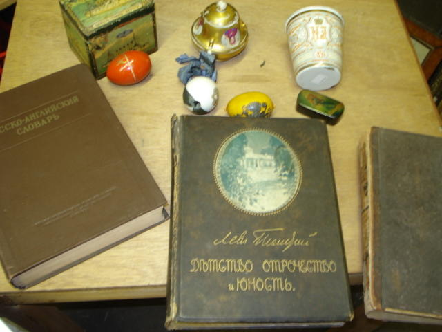 A collection of Russian objects, mostly 19th Century, comprising a Commemorative enamel beaker dated 1896, a black papier mache snuff box, with painted and decorated hinged cover, a rectangular tea caddy, the domed hinged cover and sides printed with panels of battle ships and their commanders, a porcelain egg, monogrammed, 'Presented by Tzarina Alexandra to her Lady in Waiting' six other various eggs, a porcelain vessel, gilt ground, with three roundels, this would originally have hung below an icon and twelve various printed books in Russian.