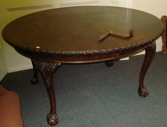 An Edwardian mahogany extending dining table, the oval top carved with egg and dart border on four well carved cabriole legs on ball and claw feet, with three extra leaves, 121cm wide x 303cm extended.