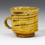 Staffordshire slipware coffee cup, combed decoration Circa 1710.