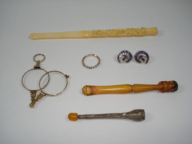 A small collection of jewellery including three cigarette holders