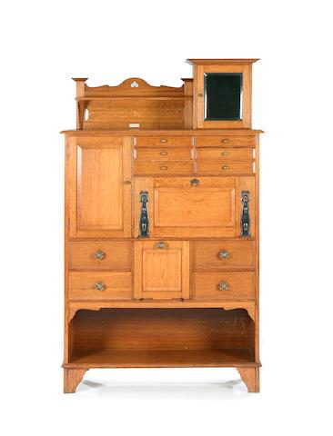 An American Arts and Crafts light oak secrètaire 'dental' cabinet Bearing ivorine label for 'Premier Cabinet Co.'