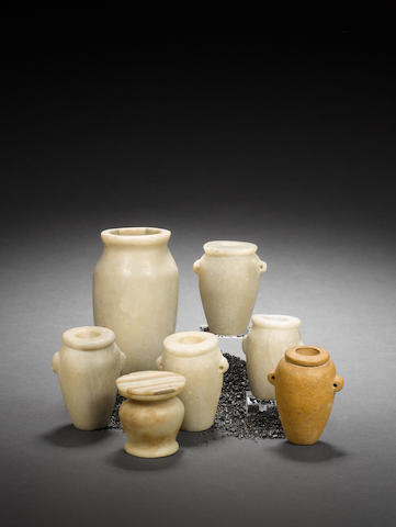8x small Egyptian stone jars and 1x lid. (9)