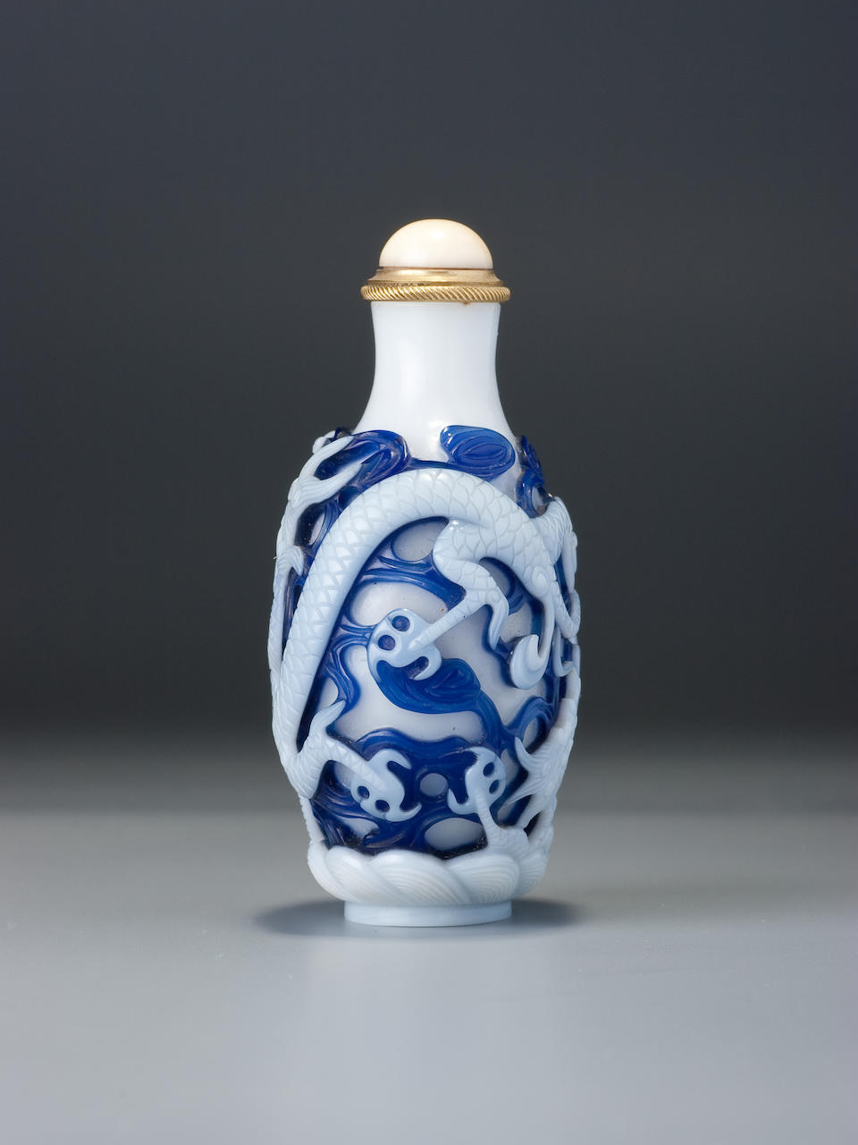 A double-overlay sapphire-blue and white glass 'dragon' snuff bottle Attributed to the Imperial glassworks, Beijing, 1760–1790