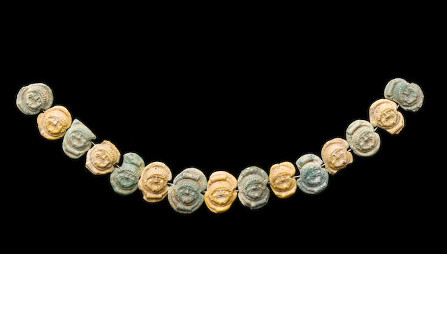 A Greek glass necklace of gorgon faced pendants