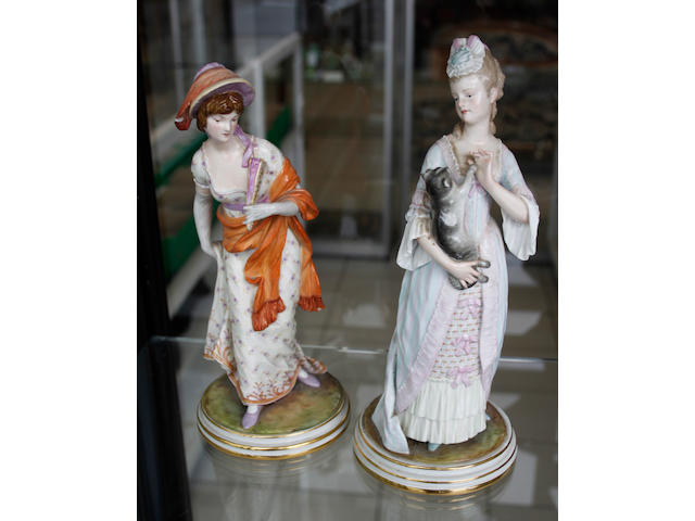 A pair of late Meissen figures of a woman holding a cat and another holding a fan, 25cm high, A/F.