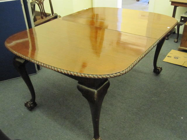 A 'Chippendale Revival' mahogany dining table, the rectangular top with four extra leaves, having a gadroon edge on cabriole legs, ball and claw feet, 350 x 121cm and a set of eight 'Chippendale Revival' carved mahogany dining chairs, with ribband vase splat backs, drop in seats, gadroon aprons, on cabriole legs, ball and claw feet to include a pair of elbow chairs.