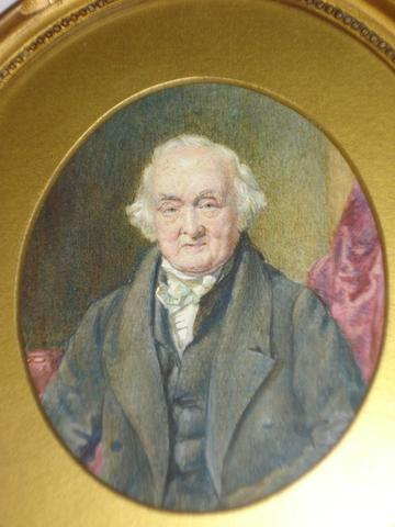 Thomas Heathfield Carrick (British, 1802-1875) A portrait miniature of a gentleman, seated, wearing dark jacket and white stock before a red drape, oval,