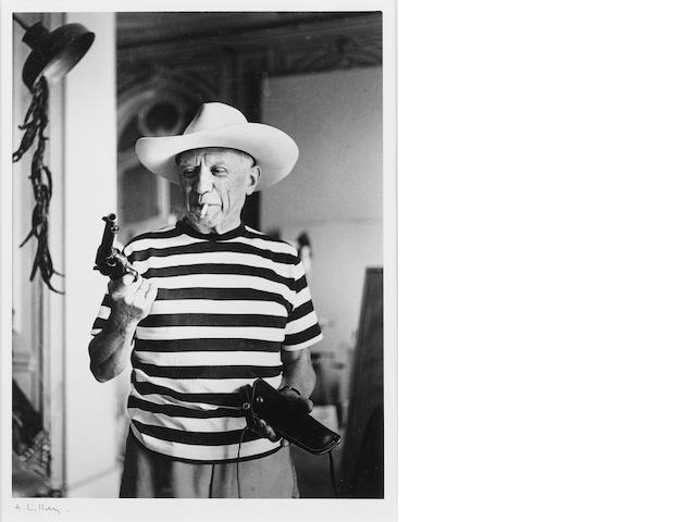 André  Villers (French, born 1930) Picasso with revolver and hat of Gary Cooper, Cannes, 1958 Paper 33.3 x 24cm (13 1/8 x 9 7/6in), image 25.5 x 19.7 cm (10 x 7 3/4in).