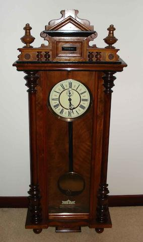 A late 19th Century walnut cased Vienna style wall timepiece,the arched moulded cresting above half reeded pilasters and a long glazed panelled door, set with a 19cm circular two piece enamel Roman dial, with subsidiary seconds, fitted with a single train movement, complete with single weight and a pendulum, 115cm high.