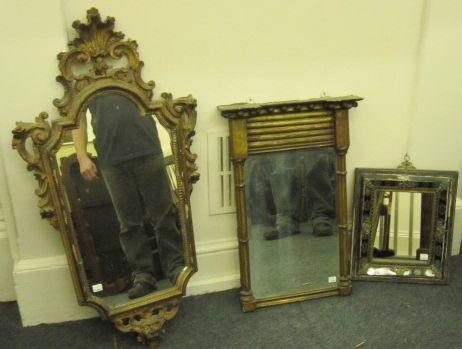 An 18th Century cartouche shape wall mirror, the moulded giltwood and gesso frame carved and pierced with flowers, 'C' scrolls, shell and mask, 93cm, a small Regency upright Pier mirror, in gilt columnar frame, and a small 19th Century marginal wall mirror, with verre eglomise slip and gilt metal mounts. (3)