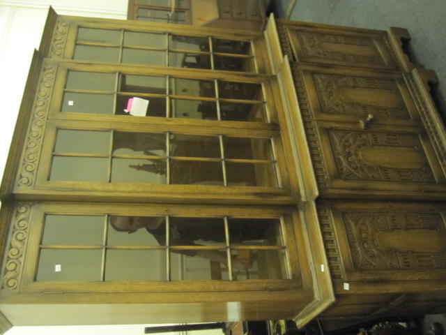 A good quality reproduction oak breakfront cupboard bookcase, the carved frieze over four astragal glazed doors on projecting base with carved panel door, and plinth base, 155cm.