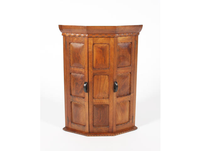 A good figured walnut hanging corner cupboard by Stanley Webb Davies, 1928