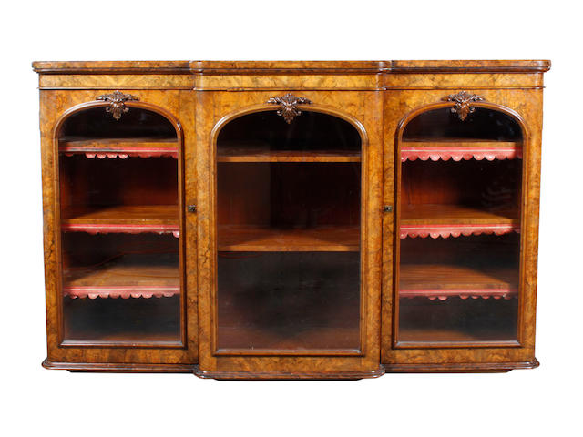 A Victorian figured walnut dwarf breakfront bookcase, fitted with adjustable shelves enclosed by three arched glazed doors, with carved leaf scroll ornament, on a moulded plinth base, 176cm.