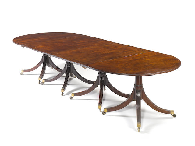 A Regency figured mahogany and ebony line inlaid four pedestal dining table