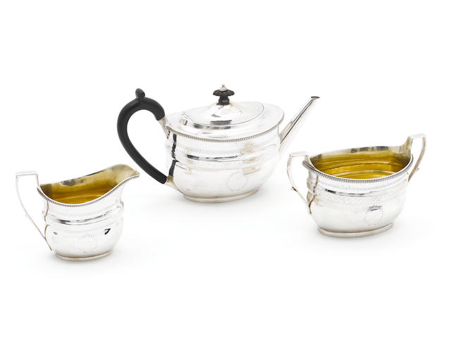 A George III silver three-piece tea service, by Robert Sharp, London, the teapot 1802, the cream jug 1801, sugar bowl: the marks are partly lost in the decoration,