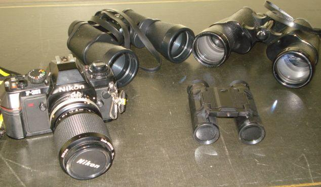 A Nikon F-301 35mm camera, and Nikkor zoom lens, case and instructions, two pairs of binoculars and a pair of field glasses. (4)