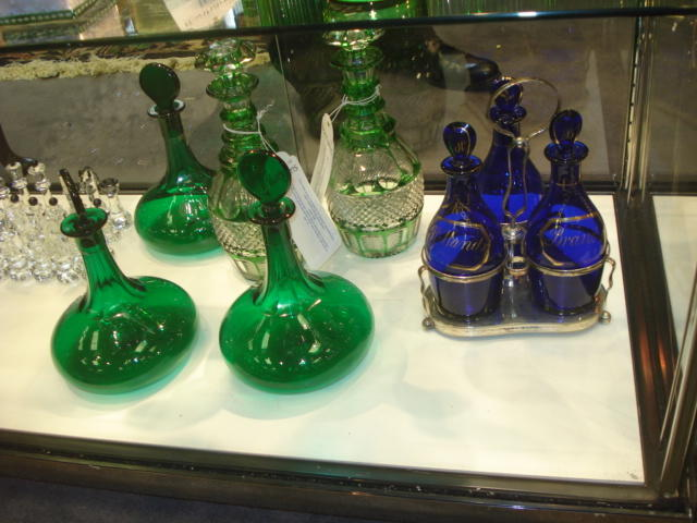 A set of three green glass spirit decanters together with a blue glass decanter and two further decanters